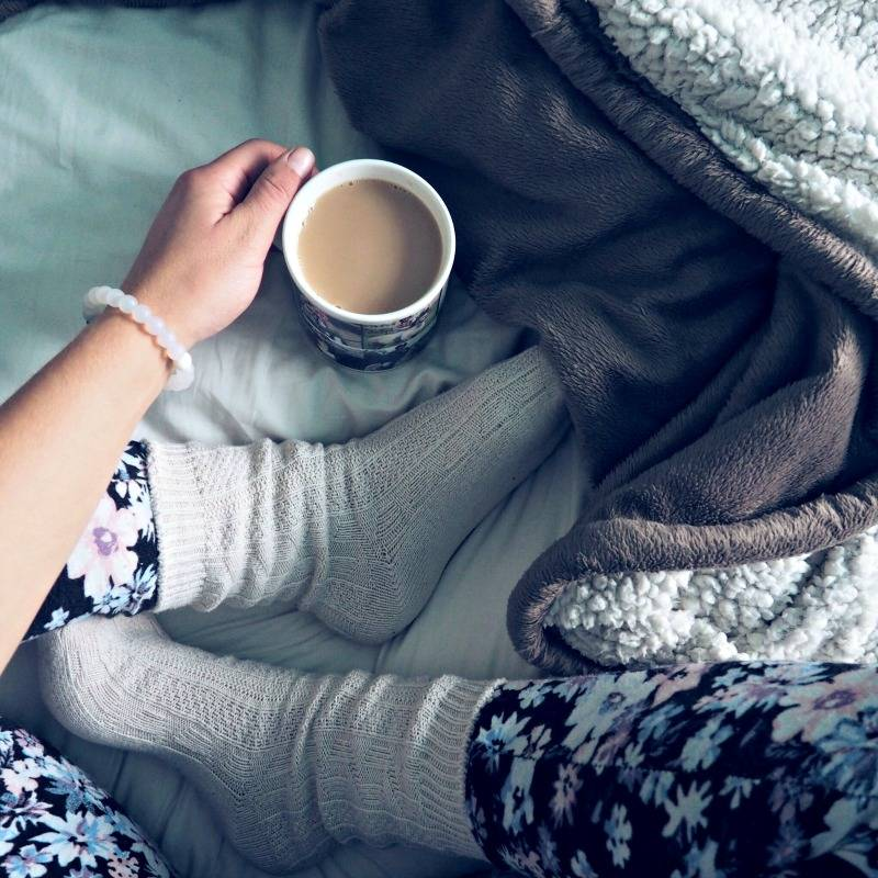 girl sat with legs crossed in bed under a blanket with a cup of tea
