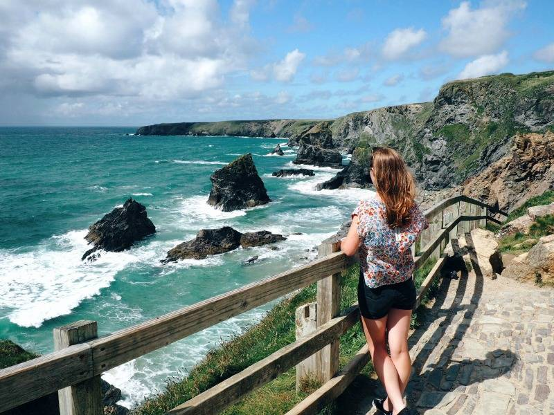Girl leaning on a fence while looking out to sea at Bedruthan Steps in Cornwall