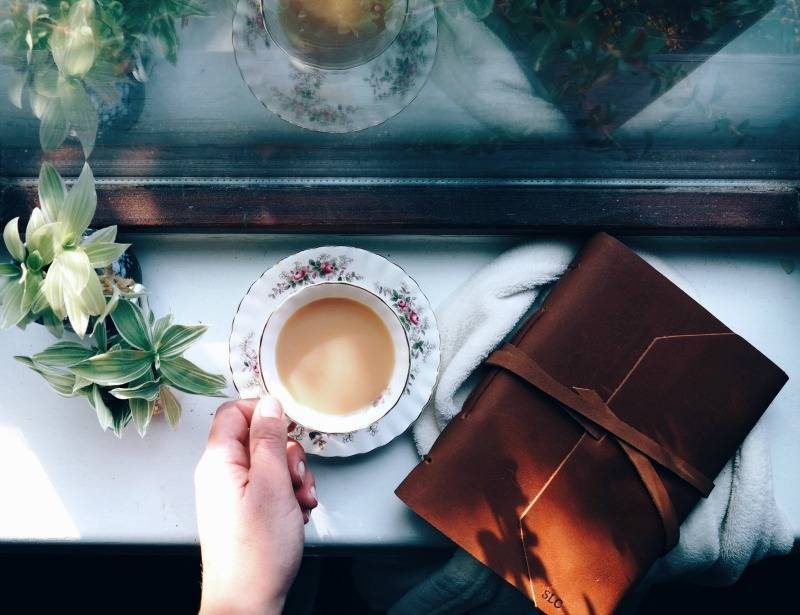 hand holding a cup of tea alongside a leather journal from Central Crafts