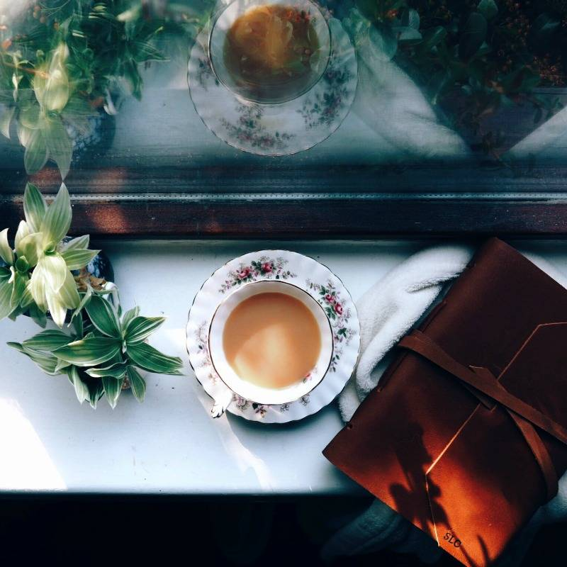 cup of tea and beatnik leather journal on the windowsill