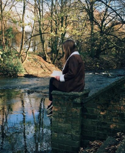 girl sat by a river reading a book