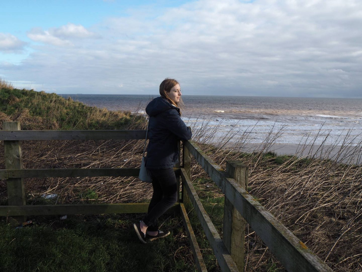 girl looking out across the beach from Mappleton Viewing Point in Yorkshire