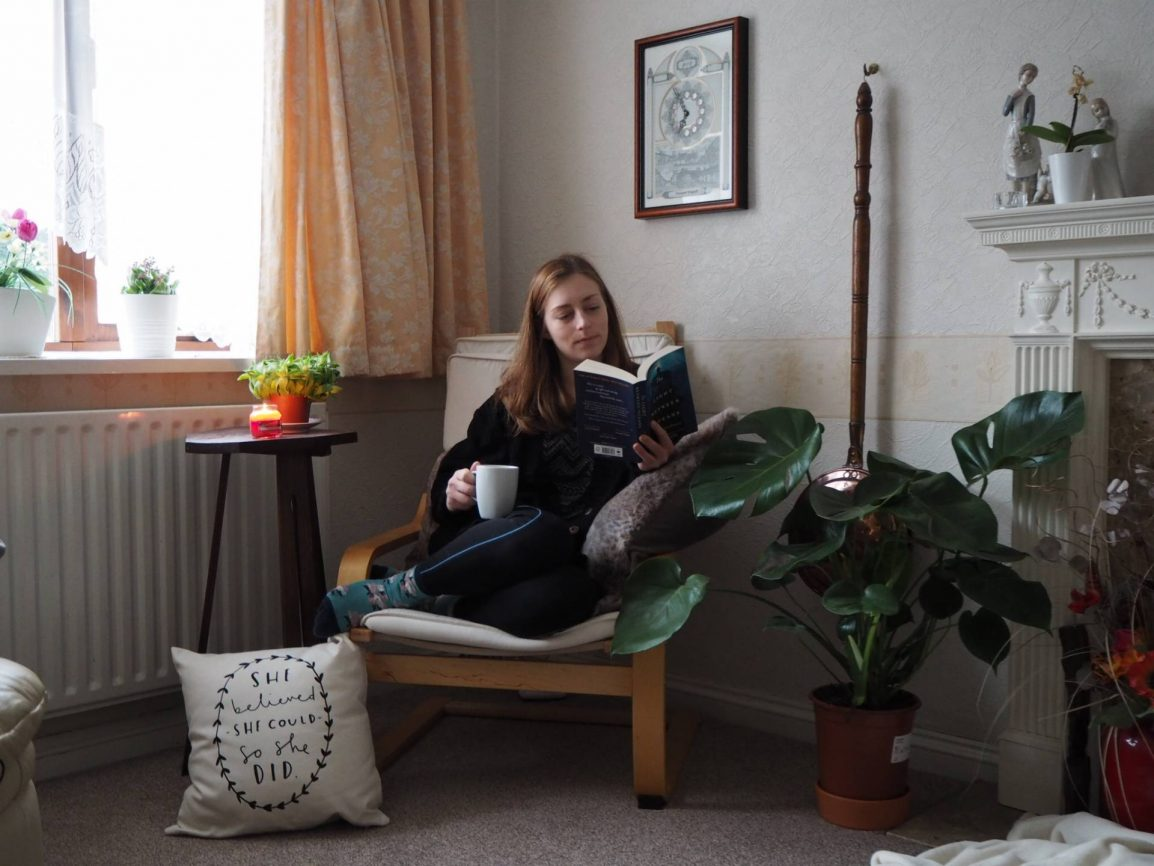 photo of girl sat reading a book with a cup of tea