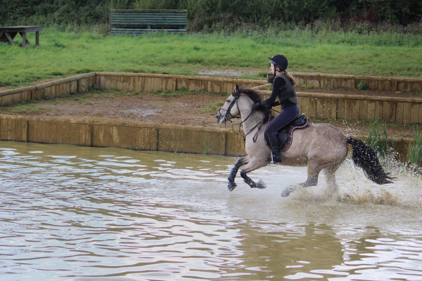Pony cantering through water on xc course