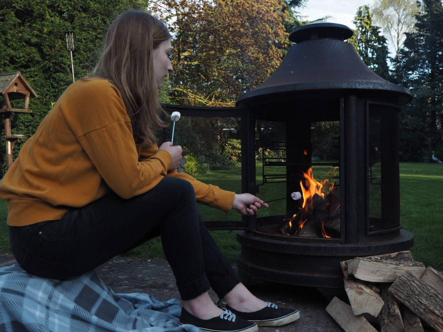 Girl toasting marshmallows on cosy outdoor fire