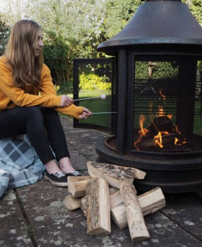 girl sat next to outdoor firepit in the countryside