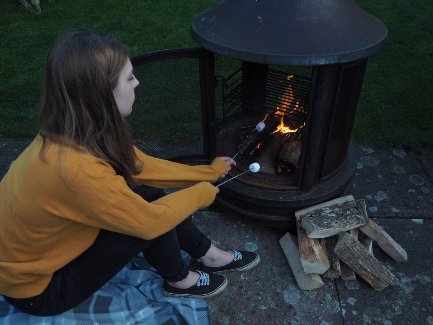 girl toasting marshmallows on open fire in the countryside