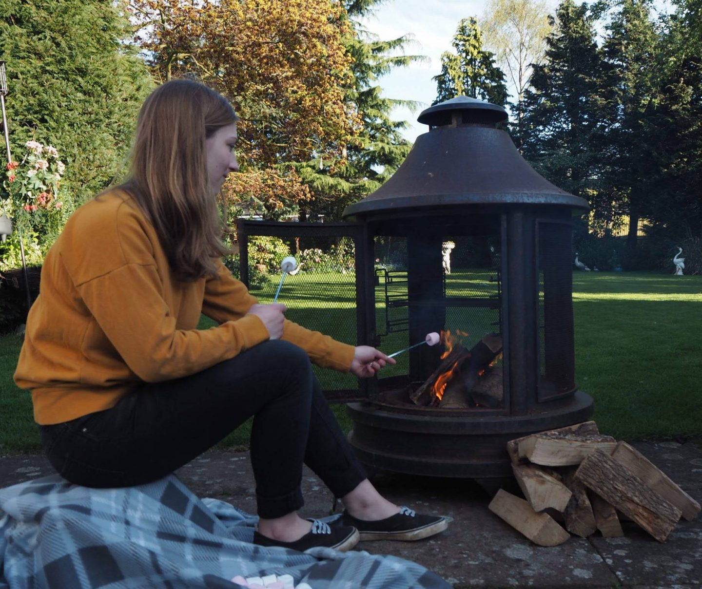 girl toasting marshmallows on open firepit