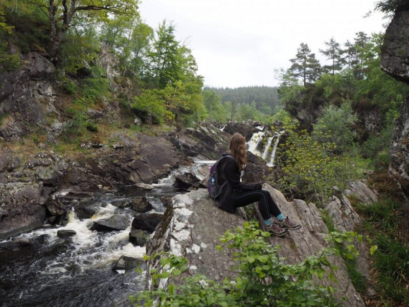 Girl enjoying walking trails around Rogie Falls in Scotland
