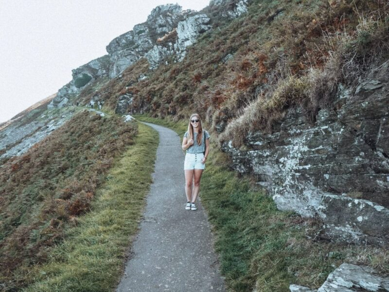 Girl walking the Valley of the Rocks coastal path