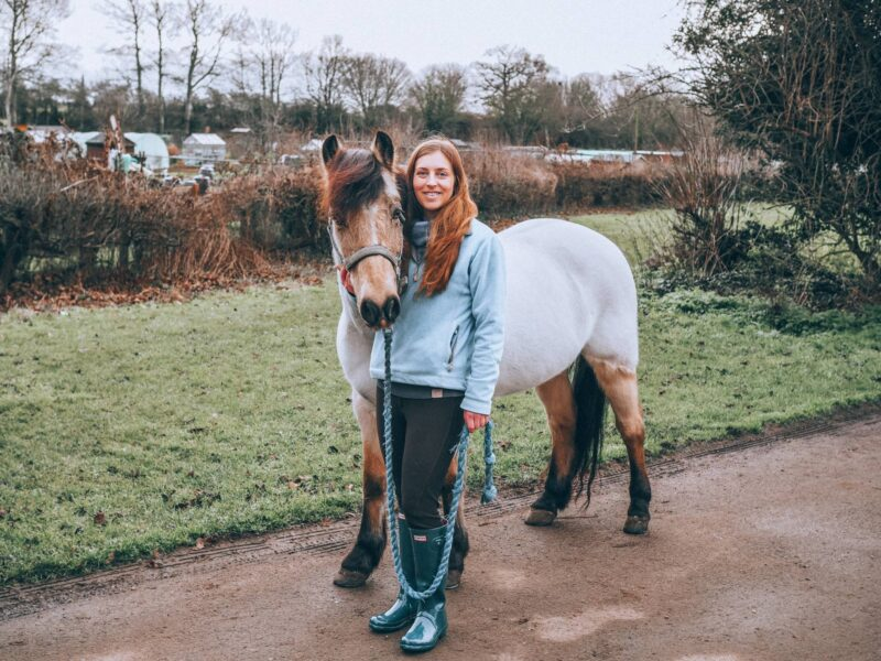 Girl leading horse in hand wearing hunter wellies