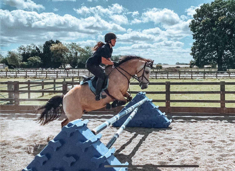 Girl jumping a dun pony over a blue coloured jump