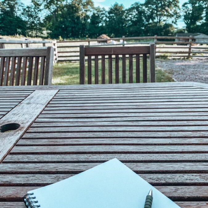 A notebook sits on a wooden table with a pen to one side and the view of a field just beyond a fence line