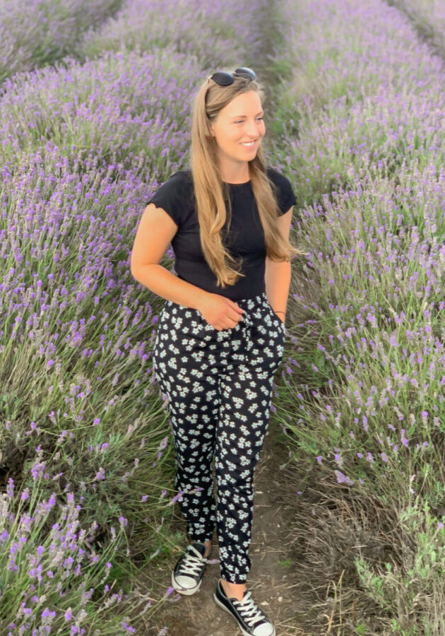A girl stands looking to the right as she is surrounded by rows of lavender, she wears floral patterned trousers, a black top and sunglasses pushed back on her head